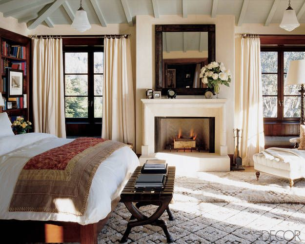 Cindy Crawford's bedroom combines traditional elements—a tufted chaise longue, dark woods, and a stone fireplace