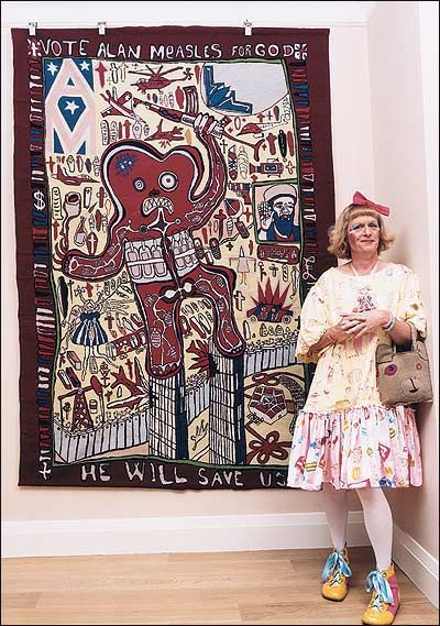 Grayson Perry, dressed as Claire, his female alter ego, beside his needlepoint