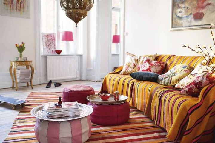 Striped Moroccan rugs, honeysuckle ottomans, and a marriage of pink and yellow, makes this a dream bohemian room. There is a Victorian side table somewhere on the far left. #home #decor #eclectic #boho #fusion