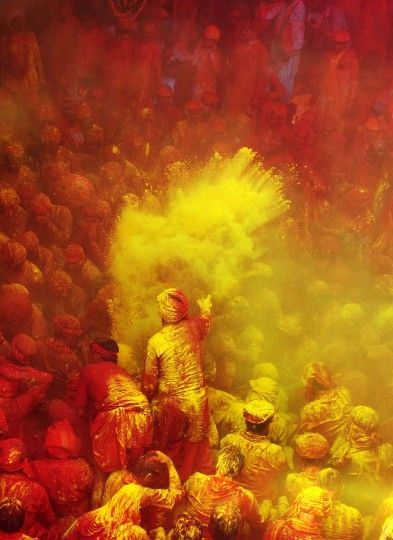 Hindu worshippers throw colored powder at the Radha Rani temple during the Lathmar Holi festival in Barsana on March 21, 2013.
