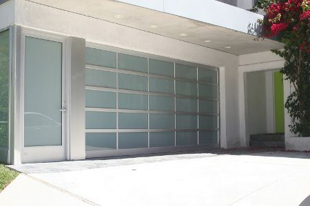 I love the design of having a glass garage door. Having the frosted glass gives you just enough privacy yet still keeps that elegant design. My only concern would be doing garage door repairs on any broken glass panels. http://www.garagedoorsvc.com/garage-door-repair/collegeville-pennsylvania/