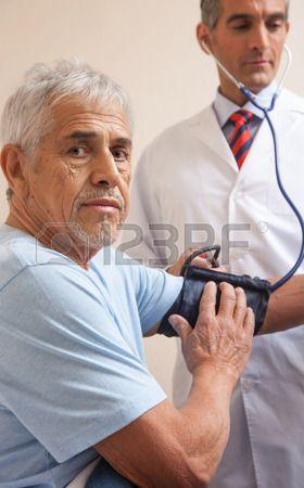 Hombre maduro en 70 de medición de la presión arterial en el hospital Concepto de la salud Foto de archivo