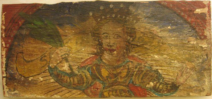 """• TAVOLA IV                               cm 43 x 19,5 x 2                       SANTA REGINA CON PALMA E CORONA Il legno del retro è in discrete condizioni, mentre la pellicola pittorica, fragile anche a causa dello spessore e dell'irregolarità dell'imprimitura, è molto danneggiata.  Figura femminile con corona a sette punte, raggiante, che tiene nella mano destra un ramo di  palma simbolo di martirio; un cartiglio giallo dietro la figura porta la scritta """"SANTA BARBARA"""", piuttosto…"""