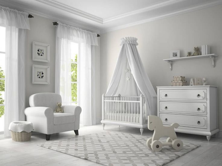An all-white nursery with floor-length daylight windows and a canopy over the crib with a star mobile.