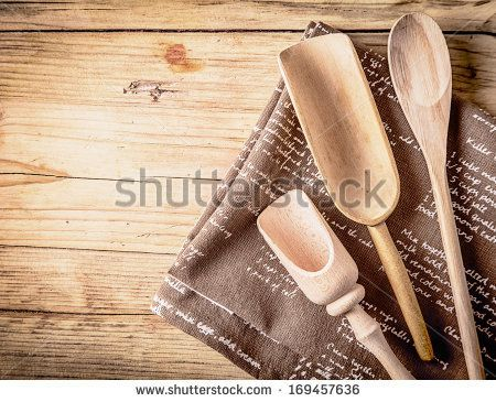 Rustic cooking utensils with a wooden spoon and two hand-carved rustic scoops lying on a folded piece of hessian on a wooden counter top in a rural kitchen - stock photo