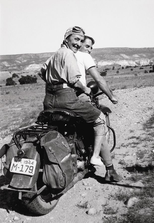 """""""Georgia O'Keeffe hitching a ride to Abiquiu, Ghost Ranch, 1944″ AKA """"Women Who Rode Away."""" –Image by Maria Chabot @Georgia O'Keeffe Museum. The painter, Maurice Grosser, visited his friend O'Keeffe's ranch in 1944. Maria Chabot photographed O'Keeffe and Grosser on his 1938 Harley-Davidson Knucklehead. It's an amazing image that celebrates denim, machine, and the joy of the open road. That look on O'Keeffe's face says it all.Harley Davidson, Artists, Georgia O' Keeffe, Ghosts Ranch, O' Keeffe Hitched, Georgia Okeeffe, Harleydavidson, New Mexico, Georgia Okeefe"""
