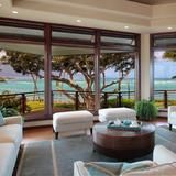 Floor-to-ceiling windows showcase gorgeous  views  of the water from the living room of this 3,250-square-foot oceanfront house. Located in Paia, Hawaii, the gated property sits on two parcels and is close to the Maui  Country  Club.  | HGTV FrontDoor