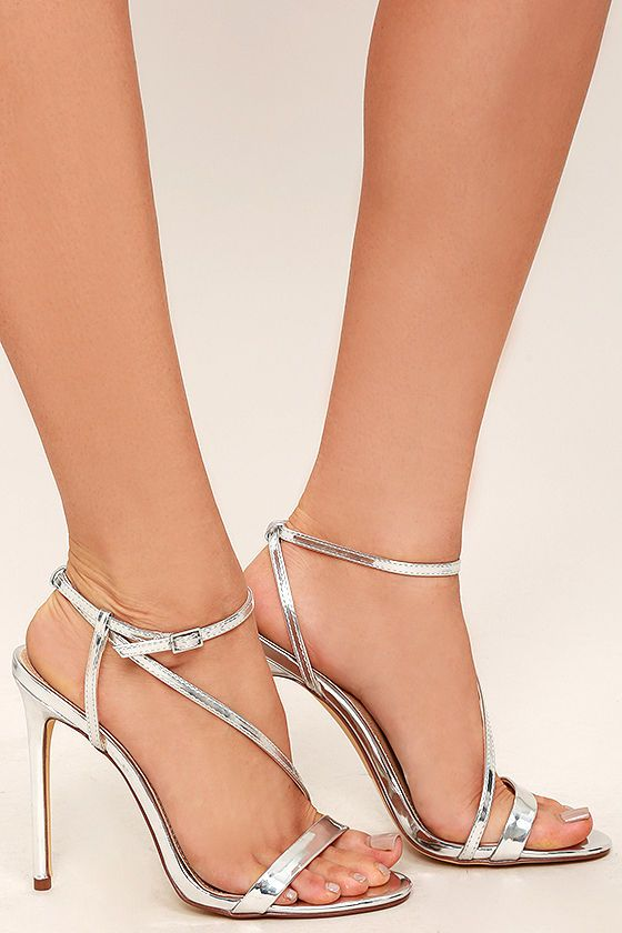 Set out in the Toulouse Silver Dress Sandals and bask in the city lights! Metallic silver vegan leather forms a toe-strap, and matching asymmetrical strap that crosses the vamp, and wraps around the ankle. Silver buckle.