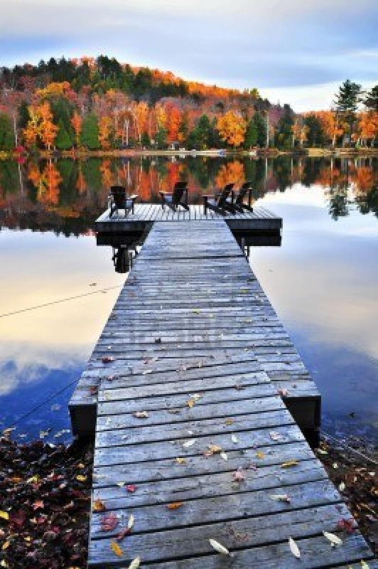 Quai en bois avec des chaises sur lac calme automne