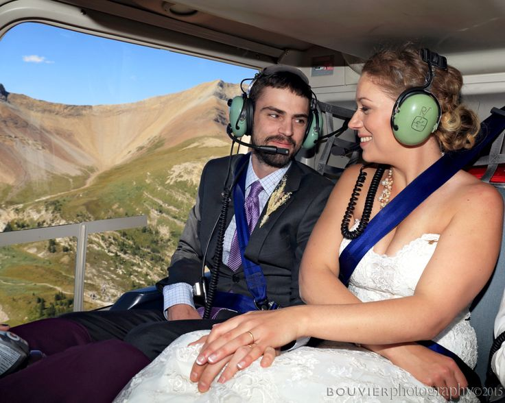 Bride & groom holding hands in helicopter flying  in the mountains of Canmore, Alberta. Summer heli-wedding. Canmore Alberta wedding.