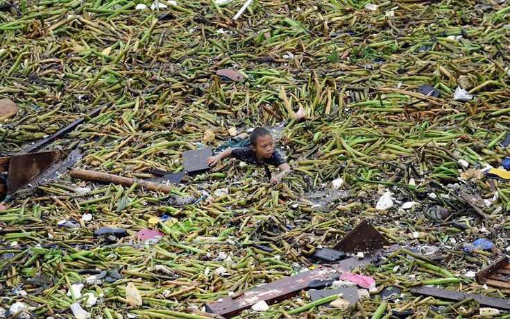 A boy swims amongst storm debris after two barges smashed into an informal settlers' area in Manila