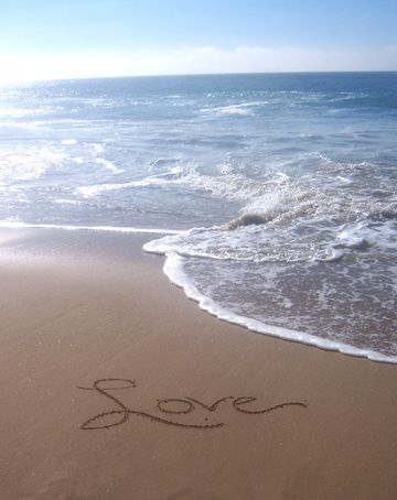 Love written in the sandy beach with I Corinthians 13 4-7 Bible…