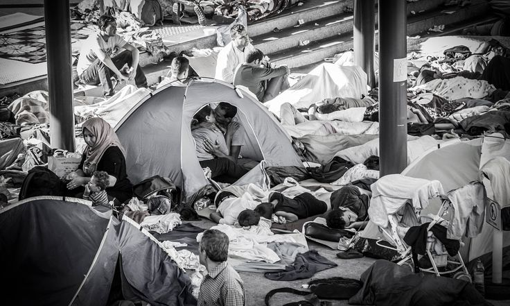 A picture of a couple kissing surrounded by a sea of refugees in Budapest has been seen by millions and offers a moving counterpart to the scenes of despair