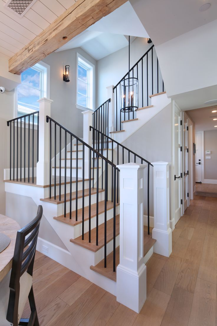Iron stair rails with white oak wood floors and overhead beams create a drool-worthy staircase!
