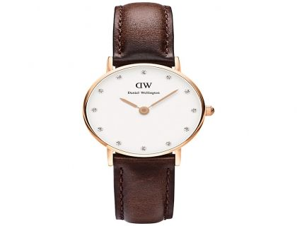 An elegant, feminine timepiece from Daniel Wellington.  A warm brown leather strap, eggshell white dial face and rose case, all combine to produce this attractive watch. The dial face has a minimal design apart from the sparkling crystal hour markers.  Brand            Daniel Wellington  Dimensions Case width: 26mm  Face Shape Round  Main Stone Type Crystal  Manufacturer's…