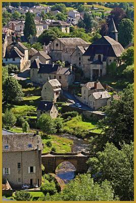 Photo du village classé de Treignac, dans la vallée de la Vézère, au-dessus du vieux pont du XIIIe siècle et des maisons en pierre surmontées de l'église Notre-Dame-des-Bans. Photos de Treignac sur Vézère, histoire des plus beaux villages de France.