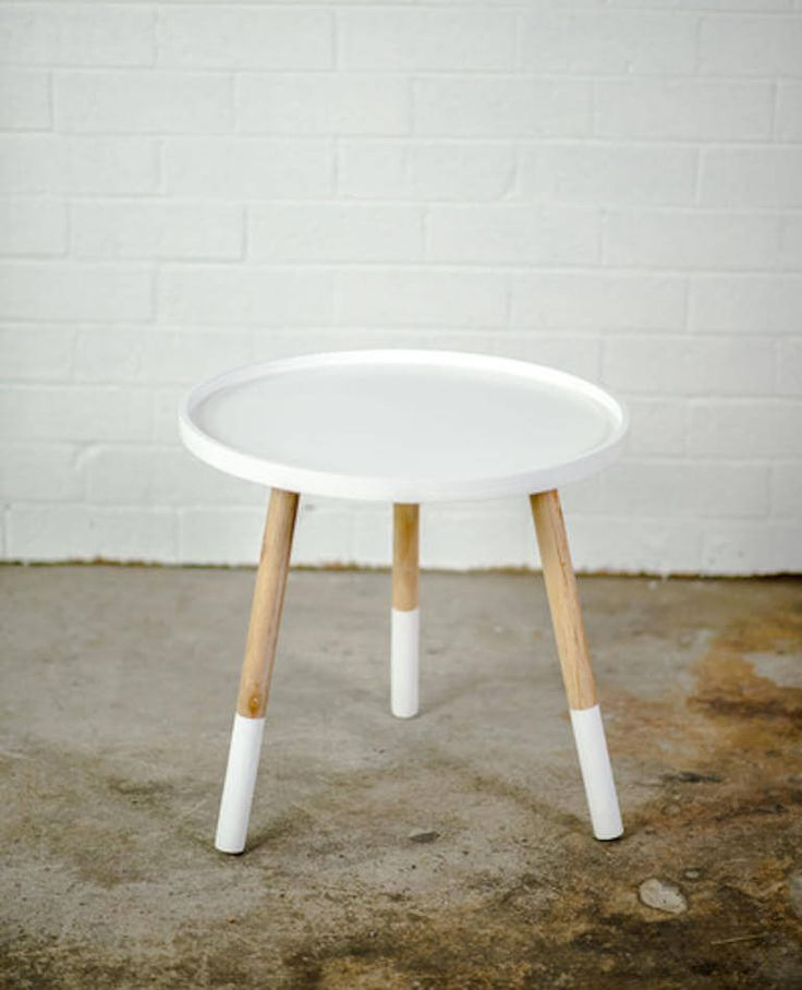 This handcrafted side table comes in a fun circular shape with raised edges and paint dipped timber legs