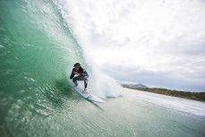 Sticky rides in a tube in fun waves at Blackhead Beach, Dunedin, New Zealand.