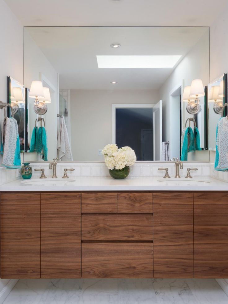 A custom walnut floating vanity by Terri Robison Design helps maximize space in this transitional bathroom while allowing more of the Akdo marble tile floor to be seen. With zero hardware on the front of the double vanity, the gorgeous grain of the wood stands on its own in the white space.