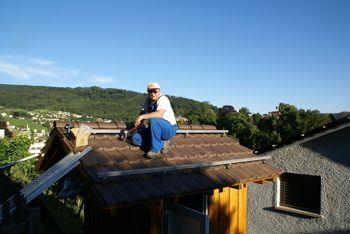 Montage der Dachhaken und Montageschienen auf dem Dach. Das ist der harte Teil der Arbeit. Aufpassen, dass man sich nicht die Knie verbrennt im Sommer!
