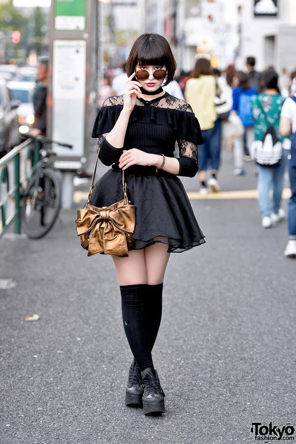 Reina is a 19-year-old Japanese student who we often see around the streets of Harajuku. Reina's dark street style features an Emoda off-shoulder top over a vintage lace long sleeve top, a black tulle skirt, Vivienne Westwood knee socks, black Converse high top platform sneakers. Her gold bow purse is by Yves Saint Laurent. Reina's favorite music artist is Tokyo Incidents.