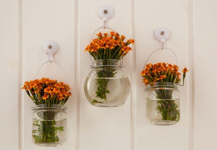 Vidros de papinha podem virar lindos vasinhos de parede. Para fazer igual, é só colocar um arame em volta da boca do vidro com o auxílio de um alicate. Em seguida, escolha as flores e encha o vaso com água.  modo slideshow