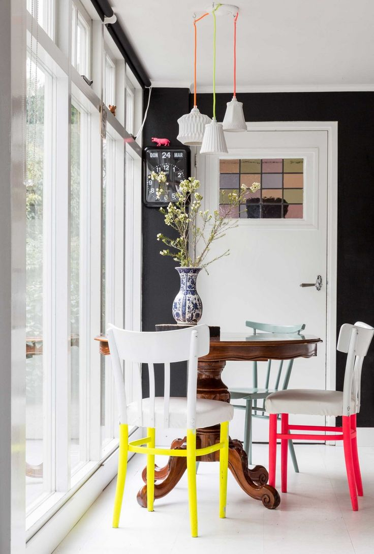 Round antique dining table with neon colored chairs
