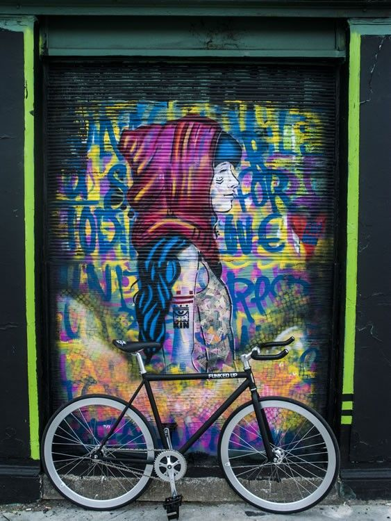 Black FunkedUp Fixed Gear Bike with Bullhorn Handlebars in front of street art in Dublin