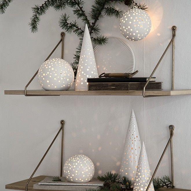 The small round tealight holder is shaped like an elegant, soft snowball, decorated with a white, highly textured glaze. The holder is covered with little, hand-made holes that allow the glow from the candle light to radiate, forming vibrant, playful patterns around the holder. Meanwhile, the opening, in which the candle is inserted, creates the illusion of a small, cosy igloo.