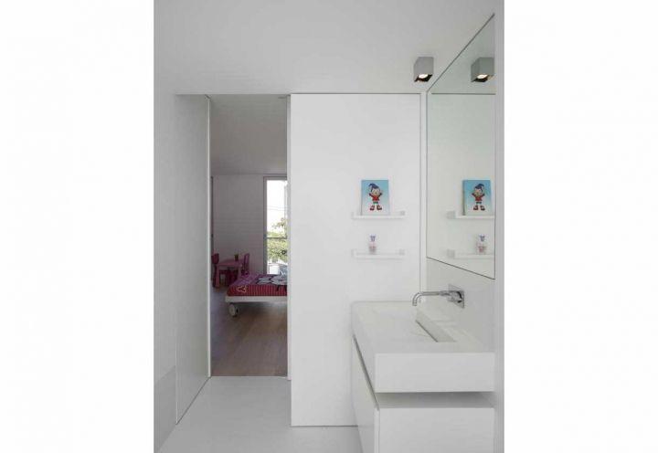 Bianco brillante anche per la seconda stanza da bagno della villetta di Parede, Portogallo. La separa dalla camera da letto dei bambini una leggera porta scorrevole, anche questa in bianco