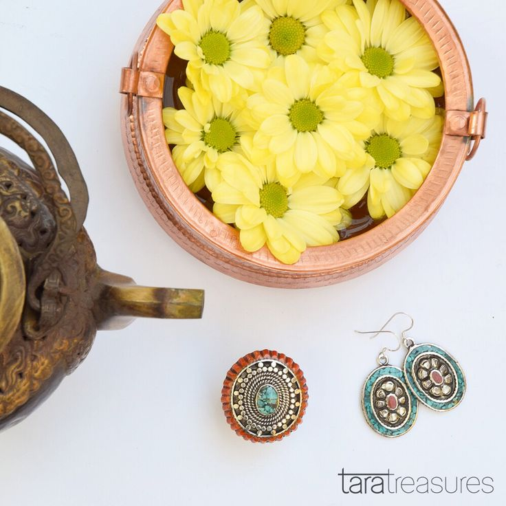 Bohemian display of yellow chrysanthemums, Tibetan teapot and jewellery.