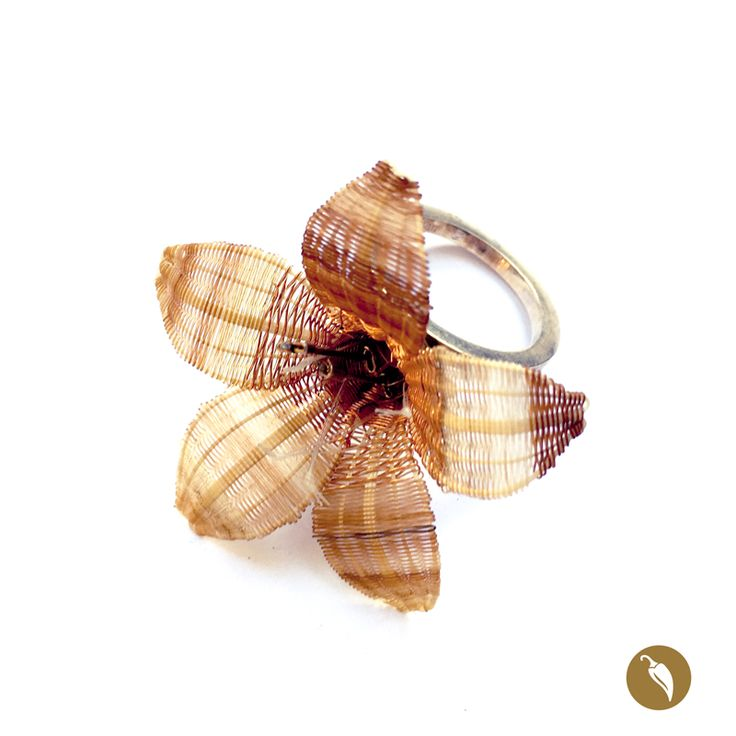Añañuca es el nombre de la flor construida en crin e hilos de cobre que se destaca en este hermoso anillo. La flor se sostiene sobre una media bola de plata. Dos de sus pistilos son de plata, lo cual otorga más brillo a la flor. Monoco es la precursora de la incorporación de la artesanía en crin en la joyería contemporánea. La diseñadora rescata este patrimonio inmaterial y lo incorpora en la joyería, fusionando el diseño y la artesanía. Autor: Monoco Colección: Flores Rari Materiales:...