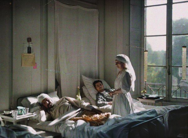 Photograph Moreuil, France | 30 July 1916.  Sunlight kisses the uniform of a nurse tending to casualties at a chateau that has been converted into a hospital at Moreuil, around 10 miles southeast of Amiens. In this autochrome, Passet's chiaroscuro lighting gives his heroine an angelic radiance.