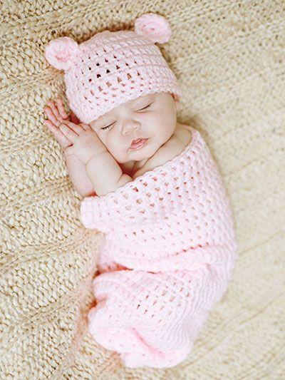 """Adorable is all you can say about this baby cocoon set! It is made using Red Heart Super Saver worsted-weight yarn. Instructions are written for size: Newborn (0--3, 3--6) months. Yarn amounts: 5 (6, 8 1/2) oz. Finished Size: Newborn: cocoon: 16""""L x 8""""across; hat: 12"""" circumference. 0--3 months: cocoon: 24""""L x 12"""" across; hat: 13"""" circumference. 3--6 months: cocoon: 24""""L x 12""""across; hat: 14"""" circumference."""