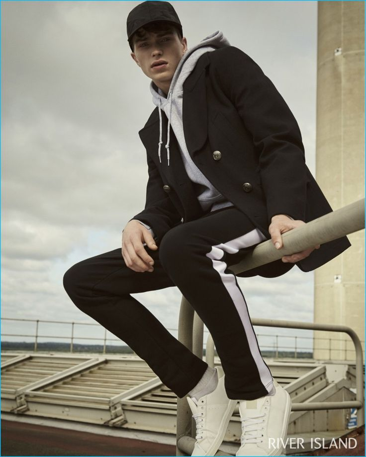 Bringing a casual edge to a navy smart peacoat, Jake Love wears a River Island sweatshirt in grey.