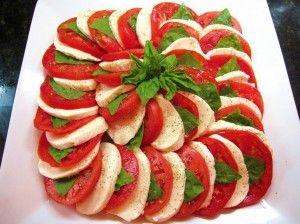 Colori e sapori tipici della penisola italiana per l'insalata caprese, i cui ingredienti sono: pomodori, mozzarella di bufala, basilico e olio d'oliva.