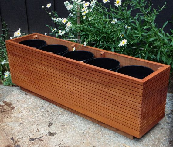 """These Mahogany planter boxes come in 10, 20, 30, 40 and 50 gallons sizes that will fit up to five 5 gallon buckets in them. You can also plant directly into them for maximum root space. Made from Mahogany my modern planter boxes are dadoed by hand for that lineal mid century style. I also make them in custom sizes and other hardwoods. Features: 1.5"""" thick Mahogany side panels, hand dadoed, glued and battened, 24-57 board feet of solid timber per planter, toe kicks, sealed for the season, 5…"""