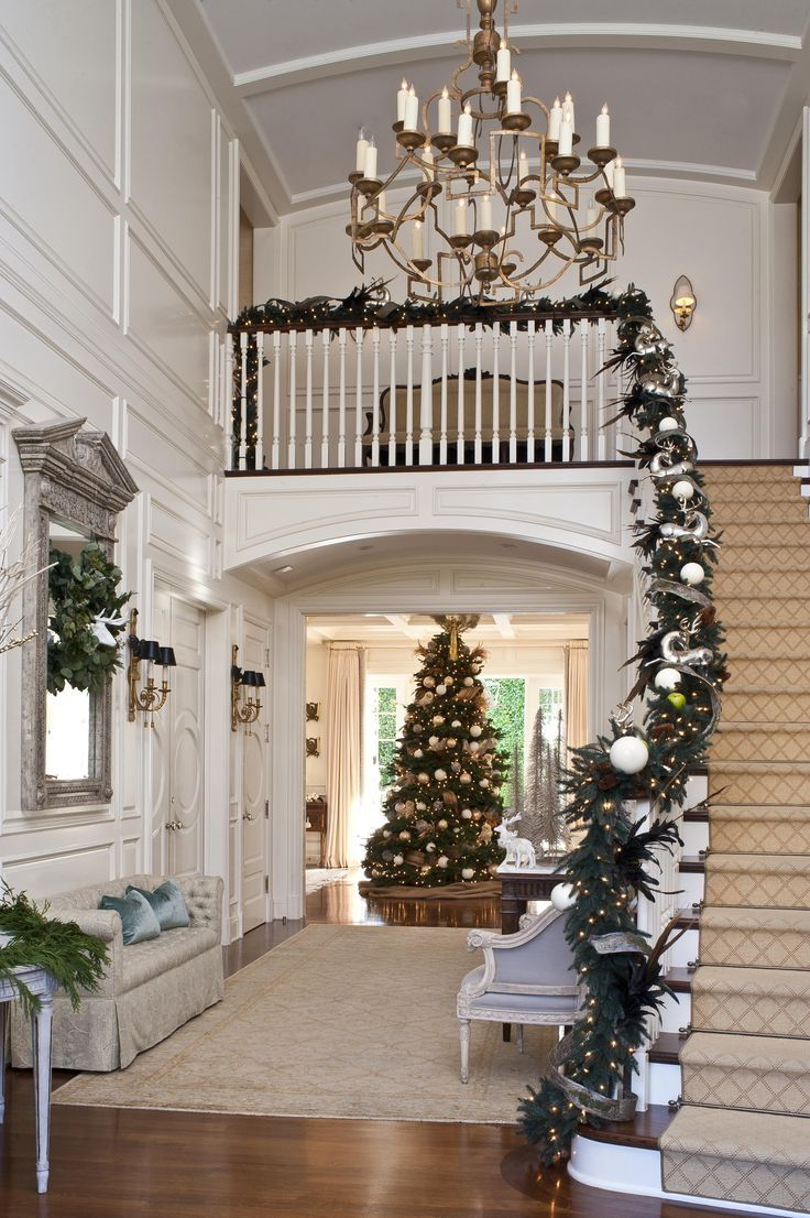 A noble fir is an immediate presence inside this grand entry. Exquisite garland graces the banister. ~ 50 Stunning Christmas Staircase Decorating Ideas - Style Estate
