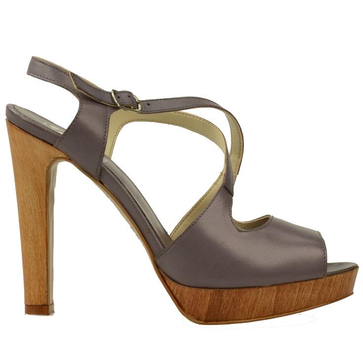 Deze hoge sandalen zijn gemaakt van leer en hebben een houtlook plateauzool en hak. Het plateau is 2,5 cm hoog en de hak is 11 cm hoog. Aan de zijkant van de enkel zit een gesp van metaal.
