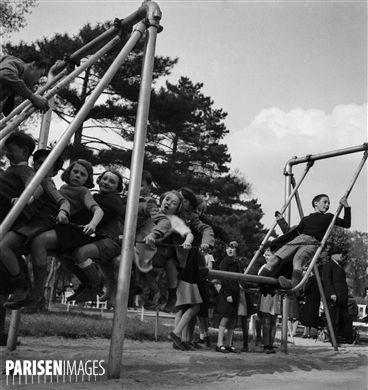 Enfants sur une balançoire, au Jardin d'Acclimatation. Paris (XVIème arr.), vers 1950.
