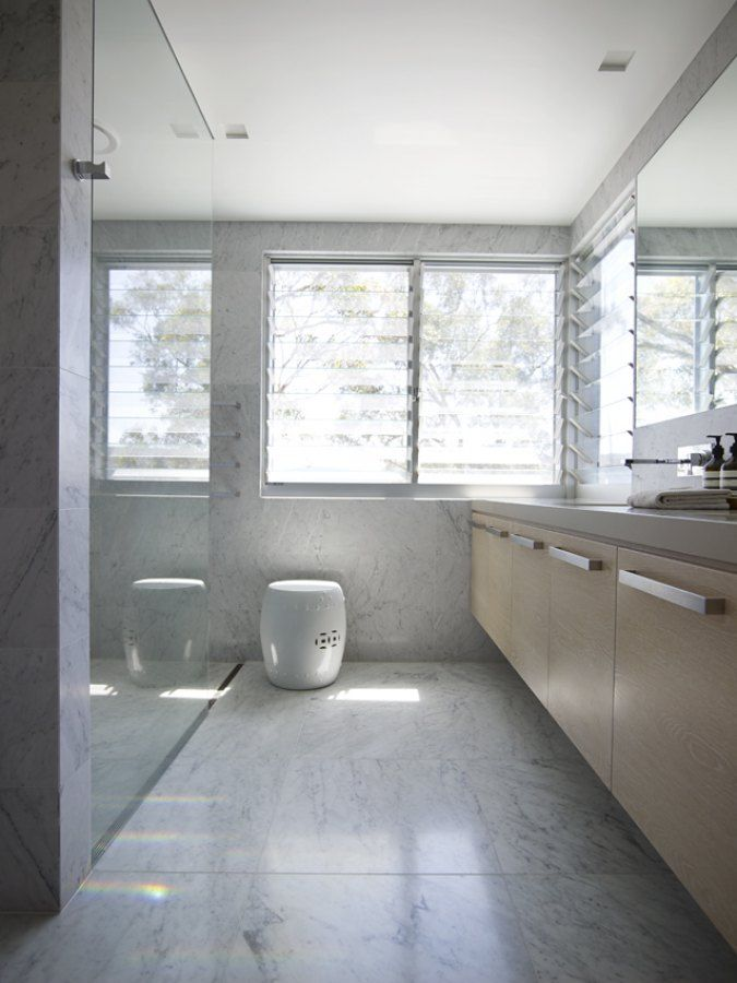 A bathroom in Avalon, Sydney by Greg Natale | Sydney based architects and interior designers. #marble #louvred windows #ceramic drum stool