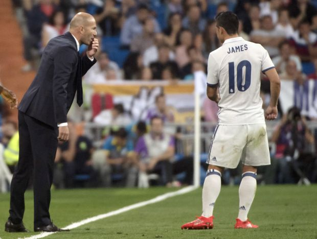 Real Madrid's French coach Zinedine Zidane talks with Real Madrid's Colombian midfielder James Rodriguez during the Spanish league football match Real Madrid CF vs Villarreal CF at the Santiago Bernabeu stadium in Madrid on September 21, 2016. / AFP / CURTO DE LA TORRE (Photo credit should read CURTO DE LA TORRE/AFP/Getty Images)