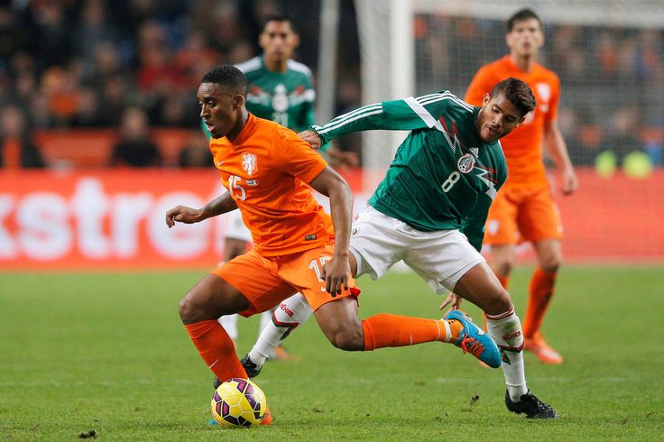Leroy Fer of Netherlands and Jonathan Dos Santos of Mexico battle for the ball during the international friendly match between Netherlands and Mexico held at the Amsterdam ArenA on November 12, 2014 in Amsterdam, Netherlands.