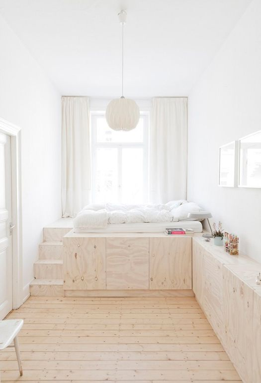 lovely white room with a raised bed, plywood cabinets and lots of light