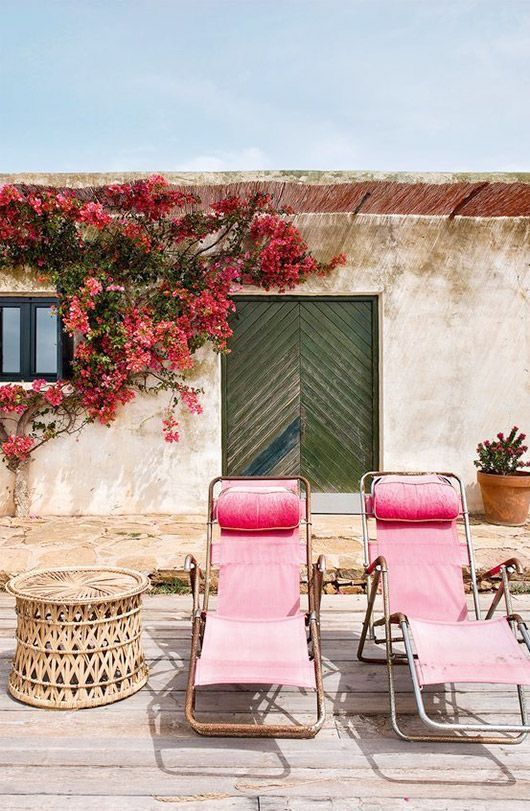 gorgeous outdoor patio space with pink lounge chairs and wicker side table. a chevron plank green door, and a wall covered in bougainvillea.