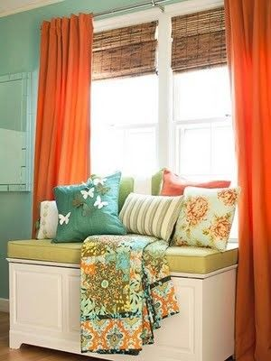 I pretty well like all of this. Robin's egg blue wall, bamboo blinds, orange curtains, and the touches of pattern & green in the seating.