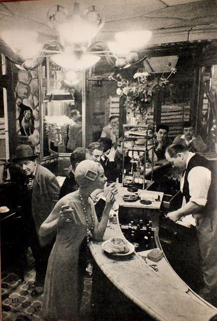 """Photographie de frank Horvat réalisée dans le restaurant """"Le Chien qui fume"""", du quartier des Halles à Paris. Le modèle est de Germaine et Jane pret à porter Jardin des modes 1957."""