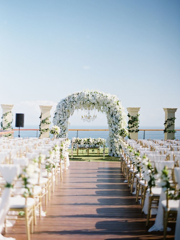 Lush white floral arbor with suspending chandelier for this bride's dream Grecian-inspired wedding // A Greek Garden Recreated: Erwin and Airin's Wedding at The Edge, Bali