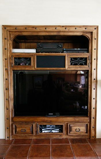 This custom rustic built-in entertainment center is made from solid alder wood, showcasing a customized speaker box. Accented by wrought iron studs and hardware, it gives off a classic Spanish look…