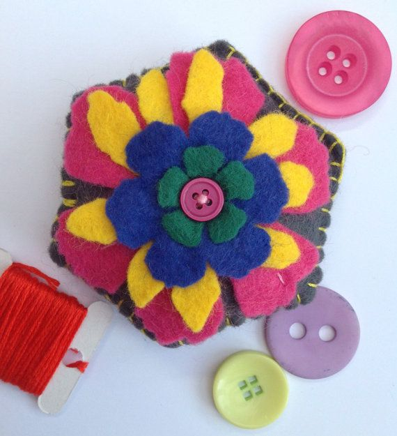 This is a hand sewn, hexagon shaped, felt pincushion with a flower motif and button detail. It can be used as a pincushion or a decoration to brighten up any home. This item measures approximately 8 cm x 8 cm and is made from high quality wool felt. Flower is cut using a Tim Holtz die, layering complementary colours of pink, yellow, blue and green to make the a beautiful flower motif, finished with a pink button at the centre. The bottom layer is stitch on to the base cushion, while the…